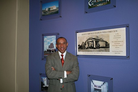 Gerald Alley in front of pictures of buildings completed by his company, Con-Real © Pryor Center for Arkansas Oral and Visual History, University of Arkansas