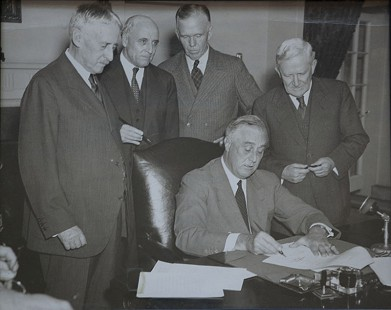 President Franklin D. Roosevelt signing the country's first peacetime selective service act, Sept. 16, 1940; from left: Secretary of War Henry L. Stimson, Rep. A. J. May of Kentucky, US Army Chief of Staff George C. Marshall, Senator Morris Sheppard of Texas © Pryor Center for Arkansas Oral and Visual History, University of Arkansas