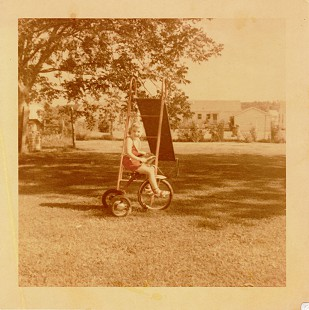 Ginger Beebe riding a tricycle in the backyard of her home in Searcy, Arkansas © Pryor Center for Arkansas Oral and Visual History, University of Arkansas