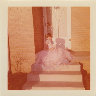 Ginger Beebe in a pink gown, seated on the front porch of her home in Searcy, Arkansas © Pryor Center for Arkansas Oral and Visual History, University of Arkansas