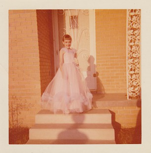 Ginger Beebe in a pink gown, standing on the front porch of her home in Searcy, Arkansas © Pryor Center for Arkansas Oral and Visual History, University of Arkansas