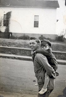 Jim Blair riding piggyback on his uncle, Charles Hugh Blair, near School and Meadow Streets in Fayetteville, Arkansas © Pryor Center for Arkansas Oral and Visual History, University of Arkansas