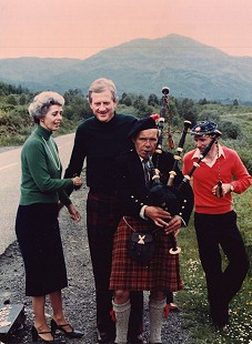 Barbara and Frank Broyles on vacation, standing with a bagpipe player wearing a Cameron of Lochiel tartan kilt © Pryor Center for Arkansas Oral and Visual History, University of Arkansas
