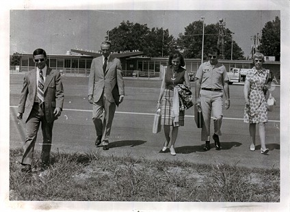 "Betty Bumpers (center) with Arkansas State Police escort, Runyan Deere, Bill Lawson, and Arkansas Department of Health employee on an ""Every Child"" trip; Pine Bluff Airport, Pine Bluff, Arkansas, 1973 © Pryor Center for Arkansas Oral and Visual History, University of Arkansas"