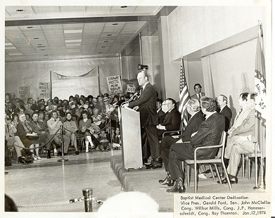 Vice President Gerald Ford making a dedication speech at the grand opening ceremony for the new Baptist Medical Center in Little Rock. Seated on the first row behind the vice president: (left to right) Congressman Ray Thornton, Senator John McClellan, Governor Dale Bumpers, Congressman Wilbur D. Mills, and Congressman John Paul Hammerschmidt; January 12, 1974 © Pryor Center for Arkansas Oral and Visual History, University of Arkansas
