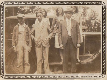 Ernie Dumas's relatives posing in front of car at Champagnolle School: (front row) cousin, Perdue; uncle, Wallace Dumas; uncle, Emon Canady, Champagnolle school teacher; (back row on running board) cousin, Ruby Armer; neighbor, Lillian Morgan; cousin, Lovie Armer; unidentified boys lying under car © Pryor Center for Arkansas Oral and Visual History, University of Arkansas