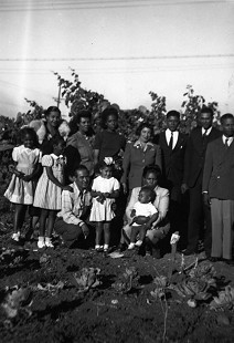 Family photo of Joycelyn Elders (front row, left) with her mother (front row, right) holding her baby brother, Chester, and her father (back row, third from right), California, 1940s © Pryor Center for Arkansas Oral and Visual History, University of Arkansas