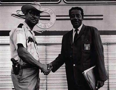 Deputy Sheriff Randall Ferguson Sr. with Garland Hegwood of Budweiser; Budweiser hired a bus to take people to Little Rock for the Grambling State-University of Arkansas at Pine Bluff football game and hired Randall Sr. to accompany them © Pryor Center for Arkansas Oral and Visual History, University of Arkansas