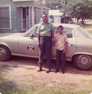Randall Ferguson Sr. with his son, John, in front of the deputy sheriff's car, June 1972 © Pryor Center for Arkansas Oral and Visual History, University of Arkansas