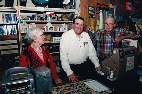 Morse Gist (right) with his wife, Jean, and Governor Mike Huckabee; Gist Music Company, Helena, Arkansas, 2002 © Pryor Center for Arkansas Oral and Visual History, University of Arkansas