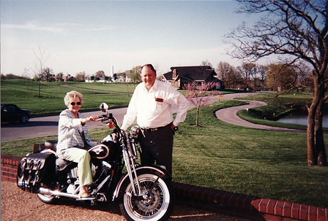 Johnelle Hunt on a motorcycle with her husband, J. B. Hunt, standing beside her on the driveway © Pryor Center for Arkansas Oral and Visual History, University of Arkansas