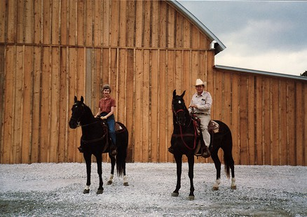 Johnelle and J. B. Hunt on horseback in front of a cedar barn © Pryor Center for Arkansas Oral and Visual History, University of Arkansas