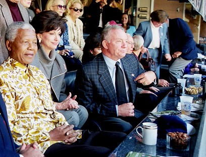 Jerry Jones with his wife, Gene, and Nelson Mandela, former president of South Africa, in the Texas Stadium owners' suite during the Dallas Cowboy's game against the Washington Redskins; October 24, 1999 © Pryor Center for Arkansas Oral and Visual History, University of Arkansas