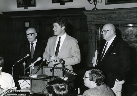 Bill Becker (standing on the left) with Governor Bill Clinton and Bob Lamb at a press conference in the Governor's Conference Room © Pryor Center for Arkansas Oral and Visual History, University of Arkansas