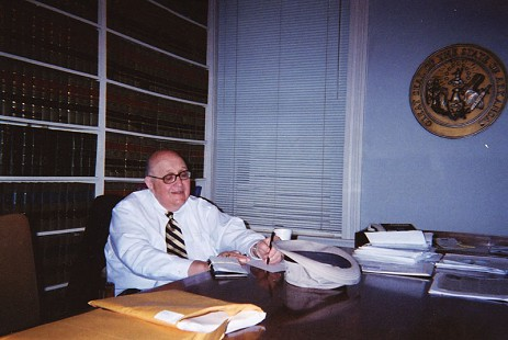 Bob Lamb seated at his desk under the state seal of Arkansas © Pryor Center for Arkansas Oral and Visual History, University of Arkansas