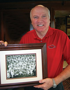 Jim Lindsey holding picture of 1964 National Championship Arkansas Razorback Football team; Lindsey, number 21 (1st row, 2nd from right) © Pryor Center for Arkansas Oral and Visual History, University of Arkansas