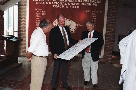 John McDonnell (center) being presented with a check from Don Tyson for $3 million that led to the construction of the Randal Tyson Track Center, 1998 © Pryor Center for Arkansas Oral and Visual History, University of Arkansas