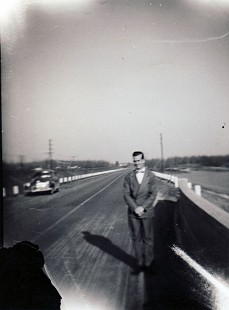 Stanley Reed's father, Eldon Reed, standing by a new highway © Pryor Center for Arkansas Oral and Visual History, University of Arkansas