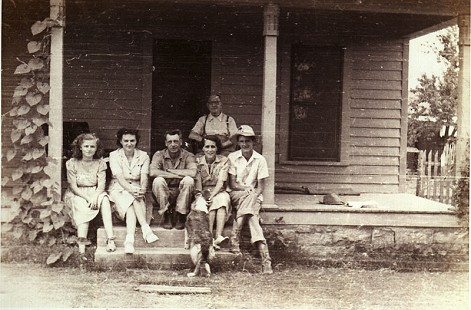 Charles Scharlau (far right) with parents, C. E. and Esther Powell Scharlau (to his right), and sister (far left) at childhood home in Mountain Home, Arkansas © Pryor Center for Arkansas Oral and Visual History, University of Arkansas