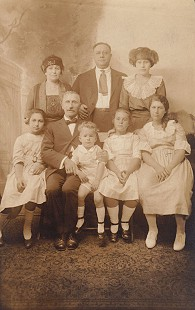 "David Solomon (front row, center) with (from left) his cousin, Kitty Elkas; grandfather, Louis Elkas; sister, Hannah Solomon; and cousin, Dorothy Elkas; (back row, from left) aunt and uncle, Beckye and Ike Elkas; and mother, Pauline Elkas Solomon; written on back of photo: ""Beckye and Ike lived in Chicago - family visited every year""; Chicago, Illinois © Pryor Center for Arkansas Oral and Visual History, University of Arkansas"