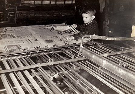 "Dorothy Stuck's son, Howard ""Buz"" Stuck III, at the newspaper folding machine in the <i>Marked Tree Tribune</i> office, 1958 © Pryor Center for Arkansas Oral and Visual History, University of Arkansas"