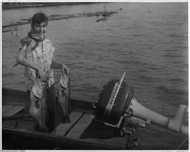 Jean Bussell (Sugg) at Storm Creek Lake where she frequently fished with her stepfather; <i>Field & Stream</i> had her display the fish, but she did not catch them; about 12 years old © Pryor Center for Arkansas Oral and Visual History, University of Arkansas