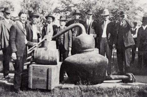 "Jack ""Papa"" Stephens (center), one of Sheriff Ed McDonald's deputies, joins in exhibiting this large moonshine still confiscated in Grant County, Arkansas, 1922 © Pryor Center for Arkansas Oral and Visual History, University of Arkansas"