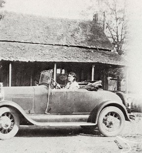 "Lois Stephens driving ""Buckles,"" Witt Stephens's first car, which he paid for by selling buckles; in background is the Lee Barnett house in Prattsville, Arkansas © Pryor Center for Arkansas Oral and Visual History, University of Arkansas"
