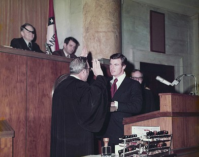 Jim Guy Tucker (at podium) being sworn in as Arkansas attorney general by Carleton Harris, Chief Justice of the Arkansas Supreme Court; Little Rock, Arkansas, 1973 © Pryor Center for Arkansas Oral and Visual History, University of Arkansas