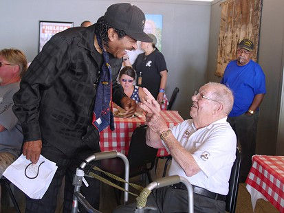 Bobby Rush (left) talks to Sonny Payne at the Bobby Rush Appreciation Day event, which was held at Southbound Pizza during the King Biscuit Blues Festival; Helena, Arkansas, 2016 © Pryor Center for Arkansas Oral and Visual History, University of Arkansas