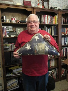 Bill W. Sutton with burial flag for his father, Keith Sutton © Pryor Center for Arkansas Oral and Visual History, University of Arkansas